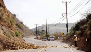 David Richardson of CalTrans photographs a rock wall where a rockslide closed Carbon Canyon Road near Carbon Canyon Regional Park in Brea, Calif., on Saturday, March 29, 2014, after an earthquake hit Orange County Friday night. More than 100 aftershocks have rattled Orange County south of Los Angeles where a magnitude-5.1 earthquake struck Friday. Despite the relatively minor damage, no injuries have been reported