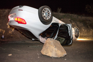 A car sits overturned on a highway in the Carbon Canyon area of Brea, Calif., Friday night, March 28, 2014, after hitting a rock slide caused by an earthquake. The people inside the car sustained minor injuries. A magnitude-5.1 earthquake centered in the area near Los Angeles caused no major damage but jittered nerves throughout the region as dozens of aftershocks struck into the night.